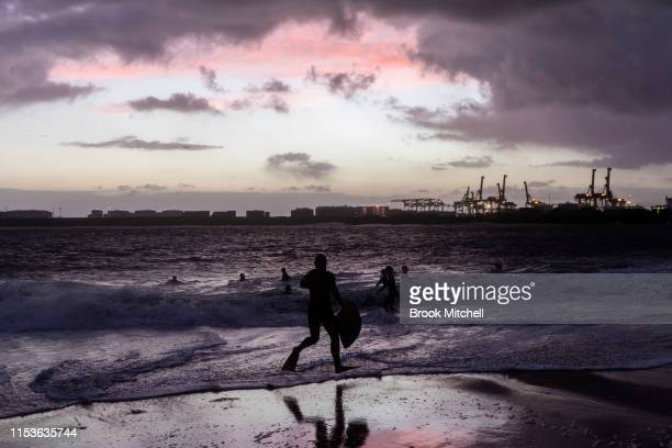 Surfers enjoy the rare surf breaking inside Botany Bay as the sun fades away on June 04 2019 in Sydney Australia The Bureau of Meteorology issued a...