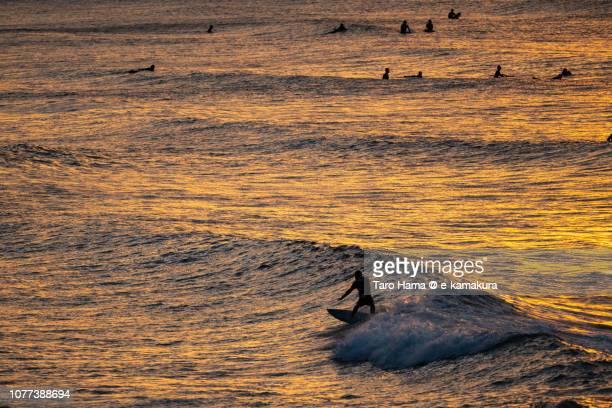 Surfers enjoying the surf on the morning beach in Kamakura city in Japan