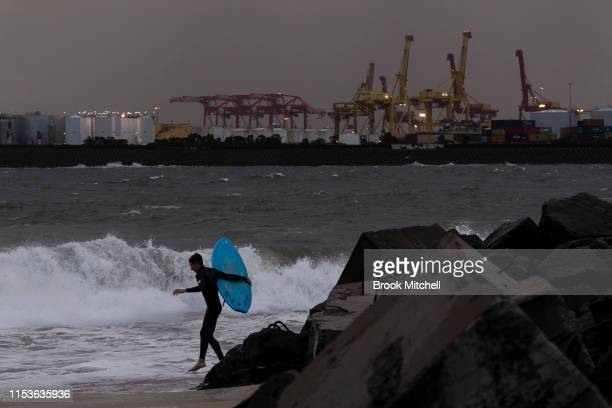 A surfers enters the rare surf breaking inside Botany Bay as the sun fades away on June 04 2019 in Sydney Australia The Bureau of Meteorology issued...
