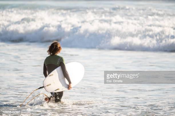surfers going for water surfing at praia da arrifana beach - algarve imagens e fotografias de stock