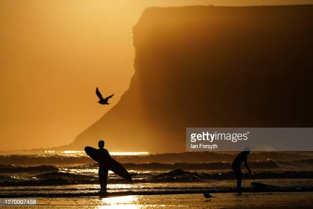 Surfers head for a dawn surf session on September 01 2020 in Saltburn By The Sea England Today will be largely fine and dry for most today with sunny...