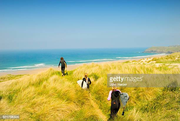 surfers heading down to perran bay - newquay stock pictures, royalty-free photos & images