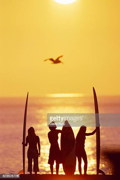 Surfers Holding Surfboards on Beach at Sunset