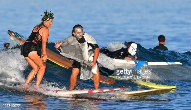 Surfers in costume participate in the 16th Annual Blackies Halloween Surf event in Newport Beach California on October 26 2019 The event is held on...