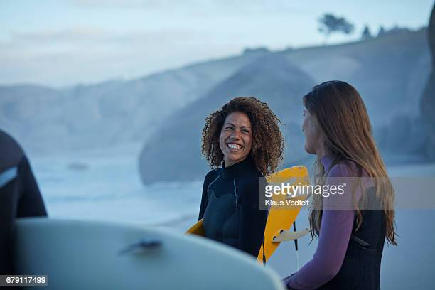 Surfers laughing togtehr at the beach