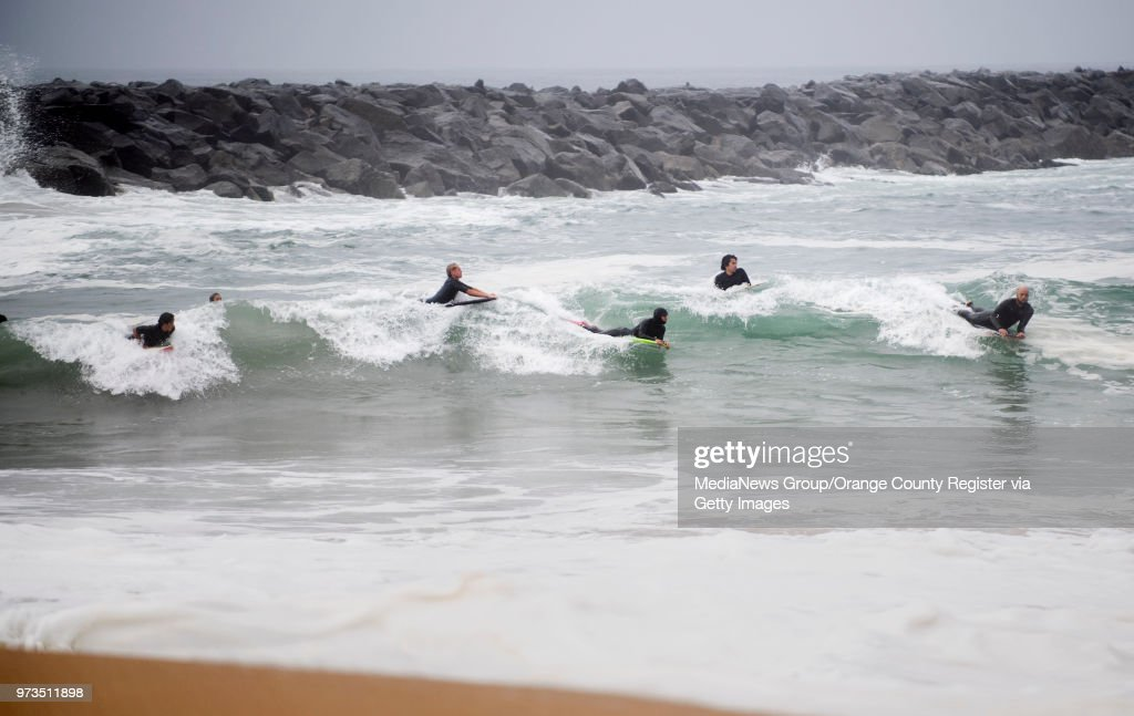 Surfers line up for a wave at the Wedge in Newport Beach, CA