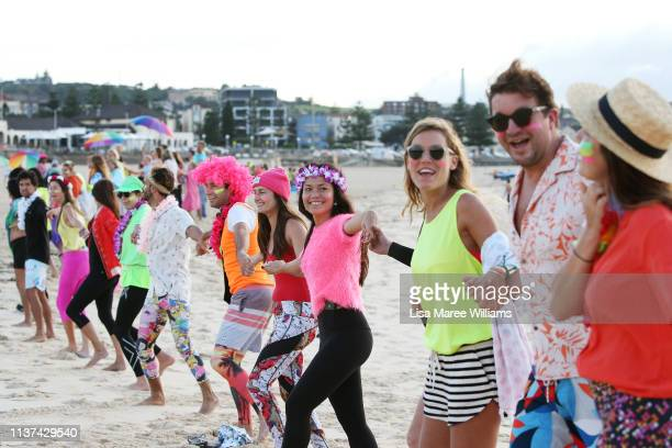 Surfers link hands in solidarity with OneWave at sunrise on Bondi Beach on March 22 2019 in Sydney Australia Surfers gather to celebrate five years...