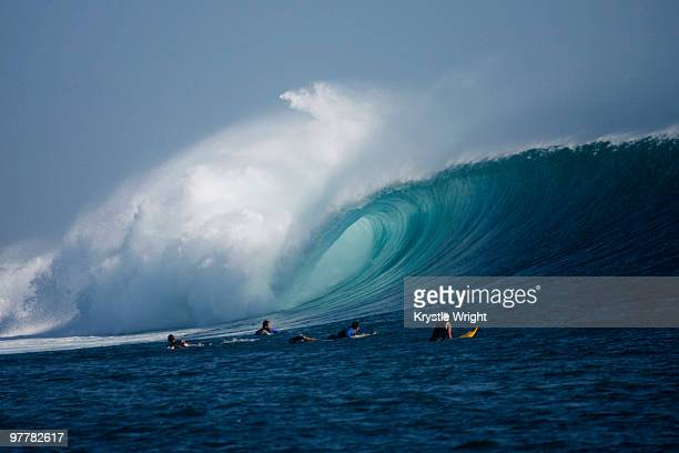 Surfers look on as a large wave rolls through at G-Land, Java, Indonesia.