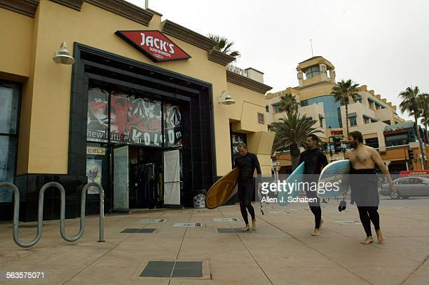 Surfers Mike Driskill of Huntington Beach left Mike Schober of La Mirada center and Leigh Gotsman of Huntington Beach walk along Jack's Surf Shop's...