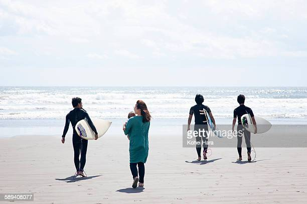 surfers, mother and baby walking on the beach