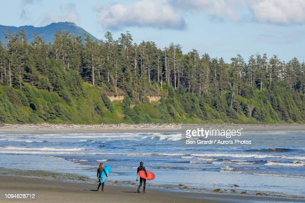 surfers on beach, florencia bay, pacific rim park, tofino, british columbia, canada - vancouver island stockfoto's en -beelden