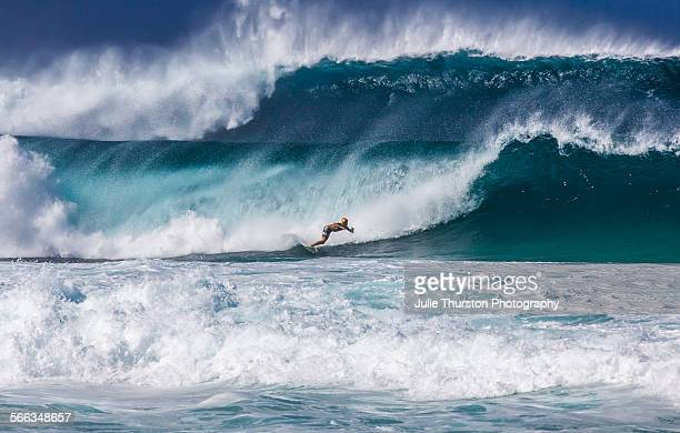 Surfers on surfboards riding huge extreme colorful teal and blue waves during a winter swell at the Pipeline at the vacation travel destination on...