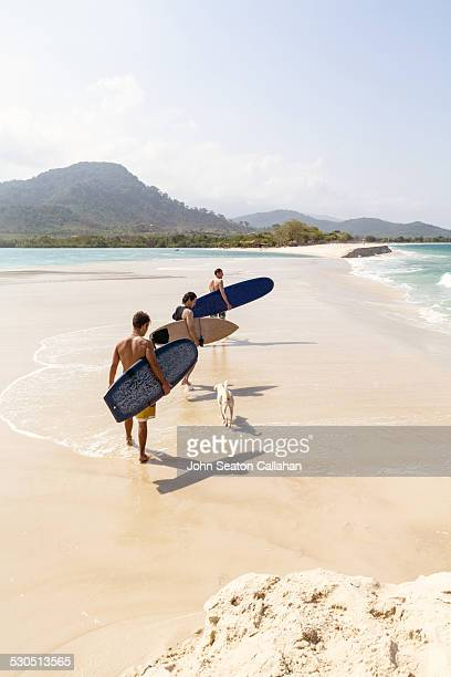 surfers on the beach at river number 2 - sierra leone stock pictures, royalty-free photos & images