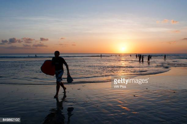 Surfers on the beach of Kuta Surfing lessons Bali