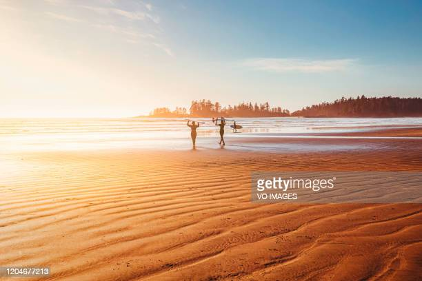 surfers on the beach walking toward the ocean. sunset time, golden hour. - golden hour stock pictures, royalty-free photos & images