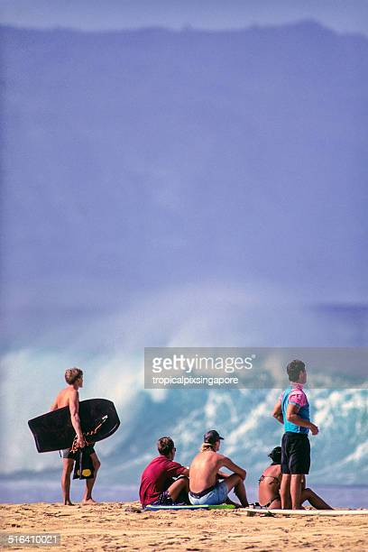 surfers on the north shore - waimea bay stock photos and pictures