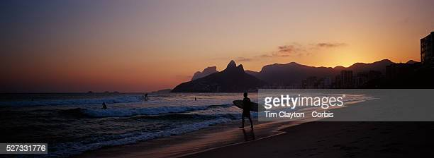 Surfers on the waters edge in a late afternoon beach scene at Arpoador Beach with Ipanema and Leblon beaches and the twin peaks of Dois Irmaos in the...