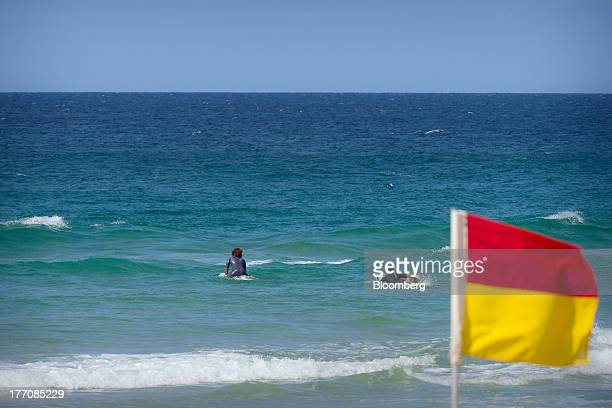 Surfers paddle out to the waves as a safety flag stands on Main Beach on the Gold Coast Australia on Saturday Aug 17 2013 The Reserve Bank of...