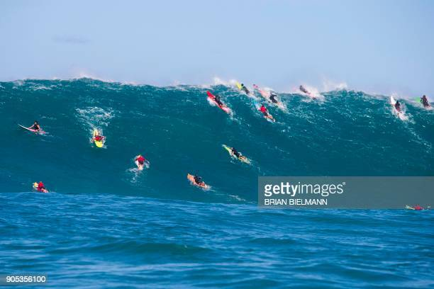 Surfers paddle over a wave at Pe'ahi, also known as Jaws, during big wave surfing on January 14, 2018. / AFP PHOTO / brian Bielmann / RESTRICTED TO...