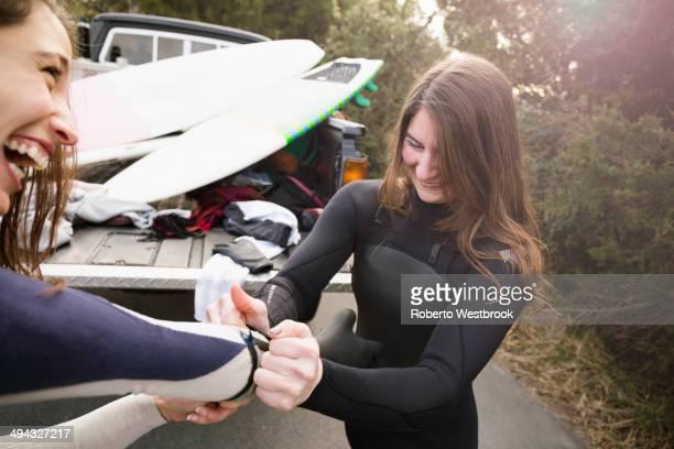 surfers pulling on wet suits by truck - traje de mergulho - fotografias e filmes do acervo