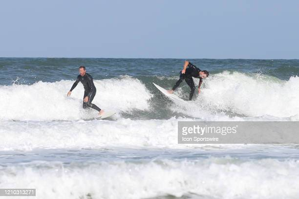 Surfers ride a wave during the beaches first open hour on April 17 2020 in Jacksonville Beach Fl Jacksonville Mayor Lenny Curry opened the beaches to...
