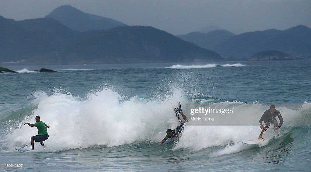 Surfers ride a wave near Arpoador Beach on March 25, 2014 in Rio de Janeiro, Brazil. Autumn has arrived in Rio bringing with it much needed rains and increased surf in some areas.