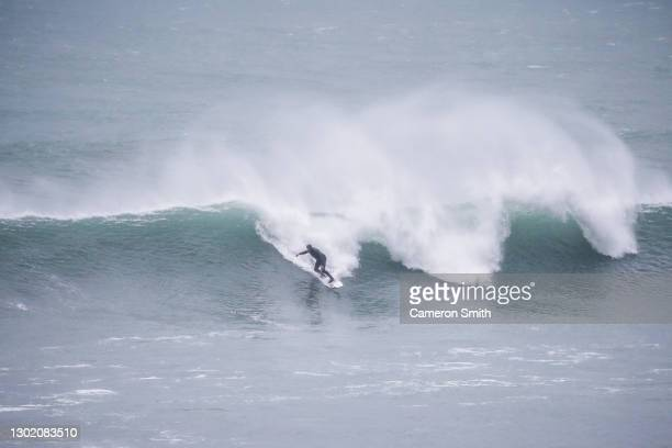 Surfers ride waves at South Fistral beach on February 14, 2021 in Newquay, England. Wintertime waves bring out intrepid surfers at beaches around...