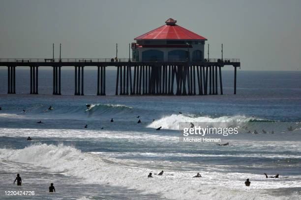 Surfers ride waves in front of the Huntington Beach pier on the beach on April 22 2020 in Huntington Beach California Southern California is...