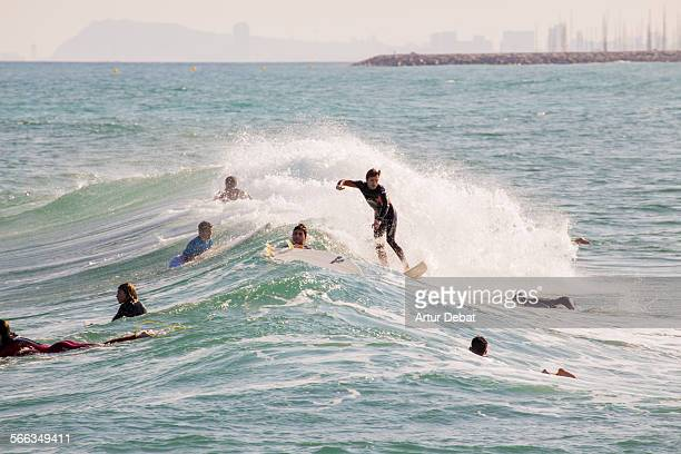 Surfers riding a wave in the Mediterranean Sea during the sunset light in the Barcelona shoreline June 12th of 2015