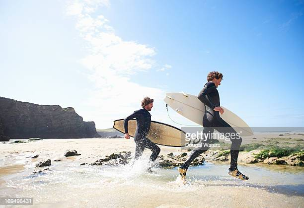 surfers running along beach. - surf stock pictures, royalty-free photos & images