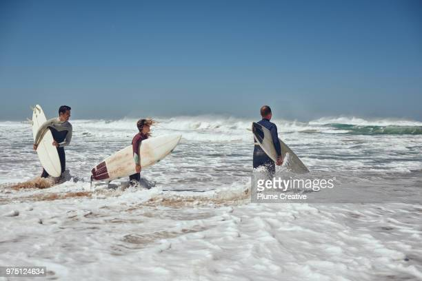 3 surfers running into surf - atlantik stock-fotos und bilder