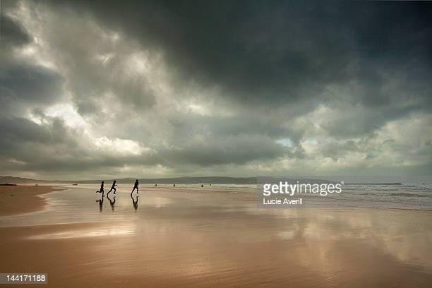 surfers running on beach - グイチアン ストックフォトと画像