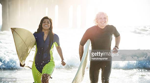surfers running on the beach entering on the water