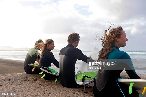 Surfers sitting by the beach chatting