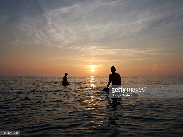 Surfers sitting on boards at sunset.