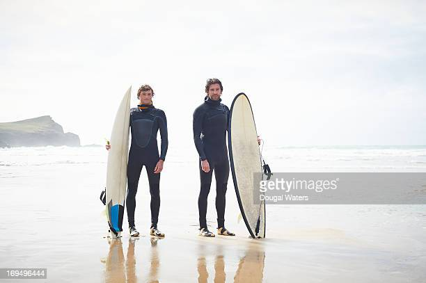 Surfers standing at beach with surfboards.