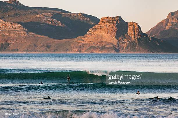 surfers sufing in the morning time - western cape province stock pictures, royalty-free photos & images