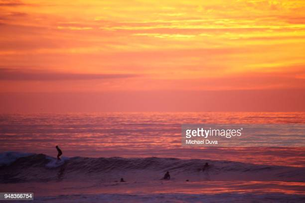 surfers surfing waves at sunset with pink sky