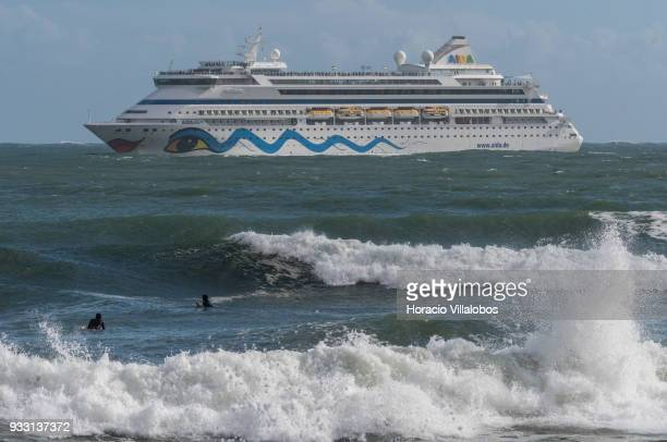 Surfers swim on the foreground while tourists are seen crowding the upper decks of Italy registered cruise ship 'AIDAvita' owned by Costa Crociere...