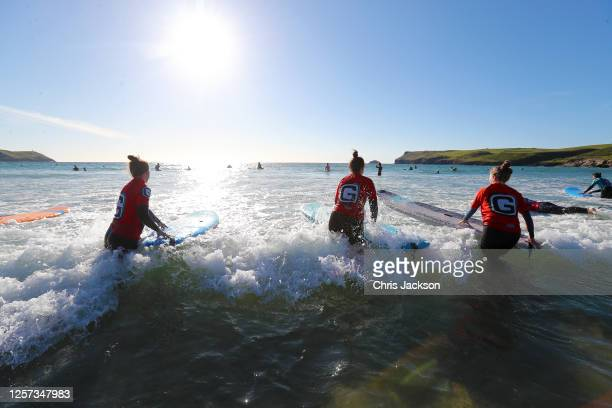 Surfers take part in a Polzeath Ladies Surf Club evening session on July 20, 2020 in Polzeath, England. Polzeath Ladies Surf Club was started in 2013...