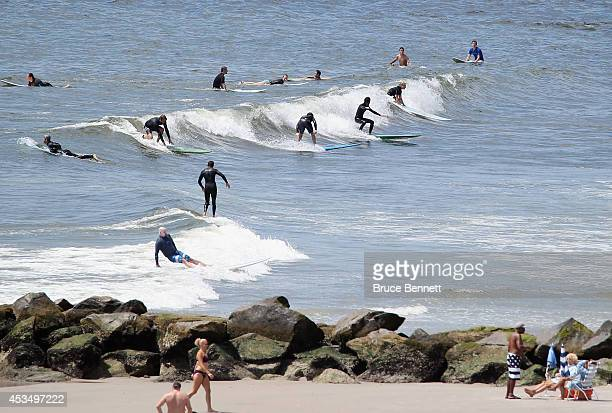 Surfers take to the water on August 9 2014 in Long Beach New York