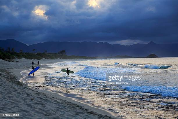 surfers under a blue sky as the sun sets - kailua stock pictures, royalty-free photos & images