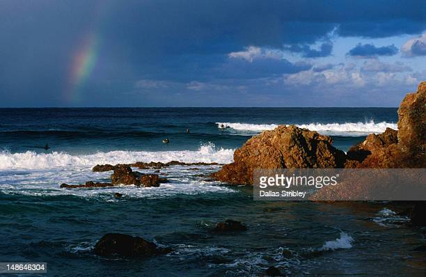 Surfers under rainbow at Flynns Beach.