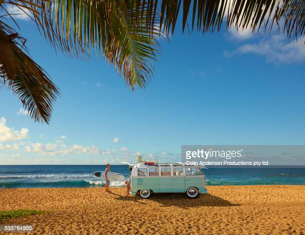 surfers unloading bus on tropical beach - mini van stock photos and pictures
