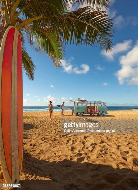 Surfers unloading bus on tropical beach