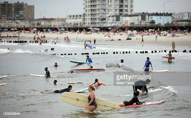 Surfers wait for waves at Rockaway Beach on August 19 2012 in the Queens borough of New York City Over the last few years the Rockaways peninsula has...