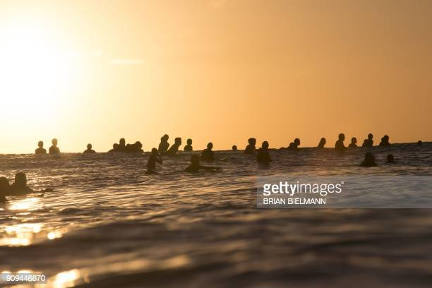 Surfers wait for waves during a late afternoon free surf session at the legendary Banzai Pipeline on the North shore of Oahu Hawaii on January 22...