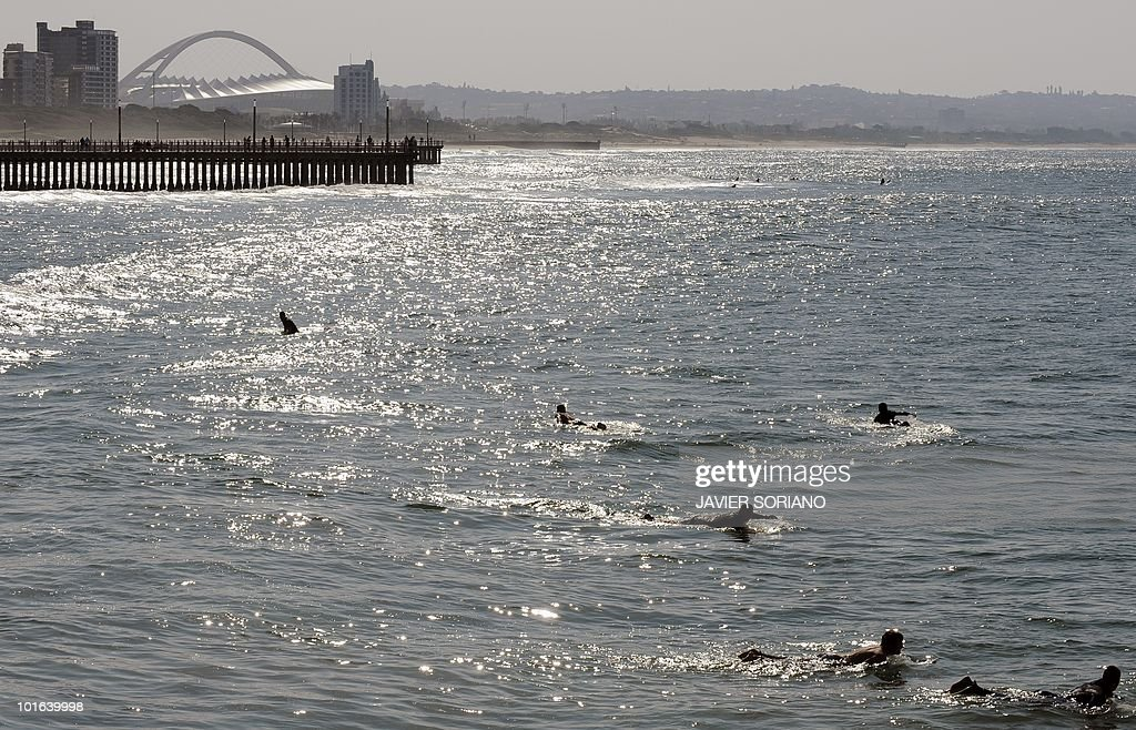 Surfers wait for waves near the Moses Mabhida Stadium (background) in Durban on June 5, 2010. Seven matches of the South Africa 2010 World Cup will be held at Mabhida Stadium.