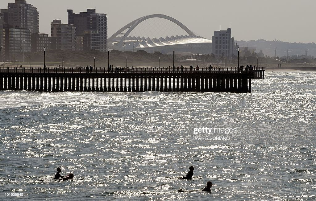 Surfers waiting for waves near the Moses Mabhida Stadium (background) in Durban on June 5, 2010. Seven matches of the South Africa 2010 World Cup will be held at Mabhida Stadium.