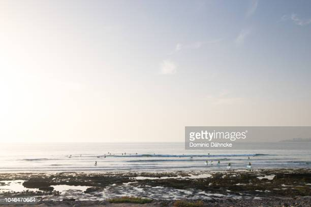 Surfers waiting waves in 'Troya I' beach in Adeje town, south of Tenerife, Canary Islands, Spain